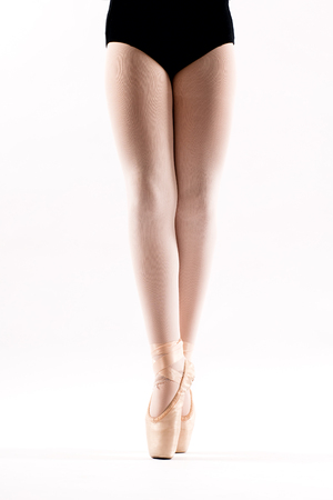 Young ballerina on pointe standing on the tips of her toes in her pink ballet shoes in a close up on her legs isolated on white