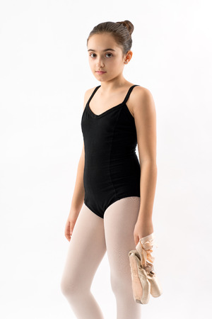 Serious thoughtful pretty young ballerina standing in a black leotard holding her shoes in one hand staring pensively at the camera isolated on white