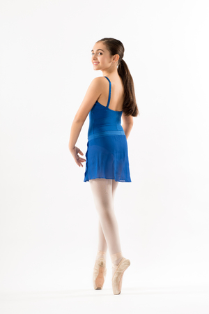 Pretty young ballerina posing on pointe in a blue dress turning to look back over her shoulder with a happy smile isolated on white