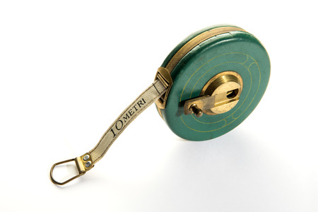 10 meter vintage measuring ribbon or tape-measure in round green body with yellow metal handle. Viewed from high angle in close-up, isolated on white background Stock Photo