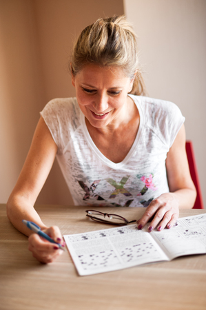 Woman in white shirt sitting at the table in the room and solving crossword puzzles, looking at open paper and smiling