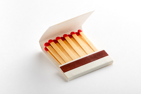 Open matchbox book, full of matches with red heads. Isolated on white background with shadow