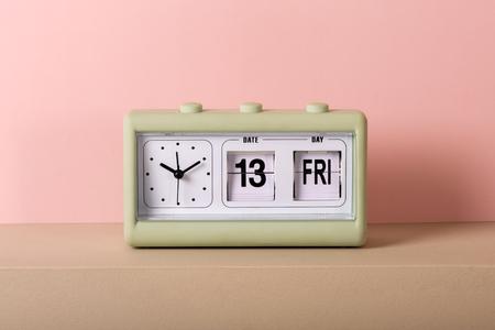 Kleine grüne Vintage-Uhr mit weißem Zifferblatt und Kalender mit Freitag, den 13. Von vorne in Nahaufnahme betrachtet, vor blassrosa Hintergrund