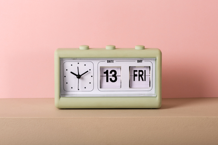 Small green vintage clock with white face and calendar showing Friday 13th. Viewed from the front in close-up, against pale pink background