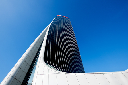 Architectural detail of the warped design of the Generali Tower by Zaha Hadid in Milan Italy in which the building twists on its central axis looking up from below against a blue sky 報道画像