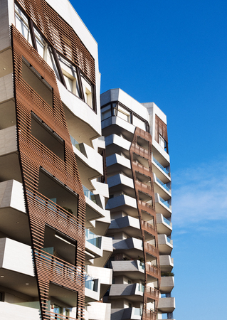 Timber cladding detail on modern apartment blocks with irregular warped angles on the building against a blue sky 報道画像