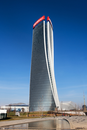 Exterior view of the Generali Tower, Milan with its distinctive warped design by architect Zaha Hadid reflected in a pool below against a blue sky