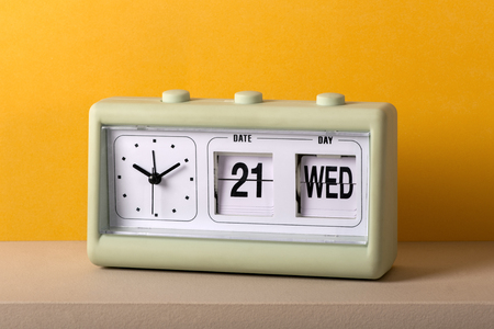 Vintage plastic tabletop clock with date, including the day in large numbers, and the time on a white dial without numerals against a colorful yellow wall Reklamní fotografie