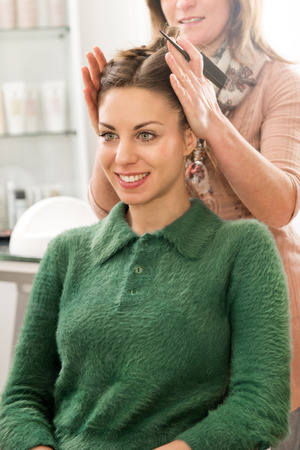 Cute smiling young brunette woman in warm green blouse sitting at hairstylist salon, during female hairdresser forming a haircut with hairbrush in her hands