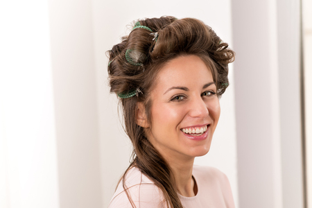 Happy laughing young woman with curlers in her long brown hair as she has her hair styled in a salon Stockfoto