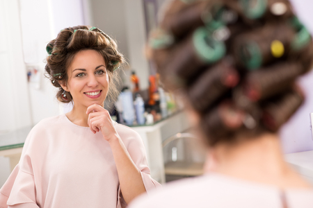 Beautiful girl with hair curlers attached to her brown hair looking in the mirror at beauty salon and smiling, having her hand to her chin