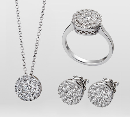 A demi-parure of gemstone jewellery in white gold or silver consisting of three matching pieces - necklace, earrings and ring isolated over a white background