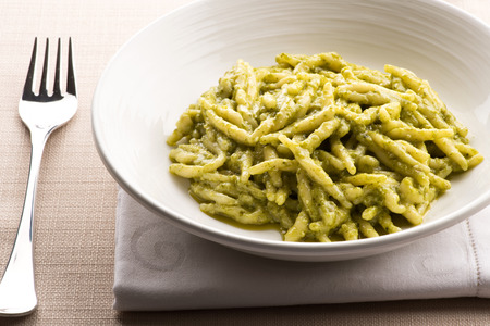 Ligurian trofie pasta, Trofie al pesto, with fresh pesto sauce served as an appetizer in a white bowl with napkin and fork for traditional regional Italian cuisine Banco de Imagens