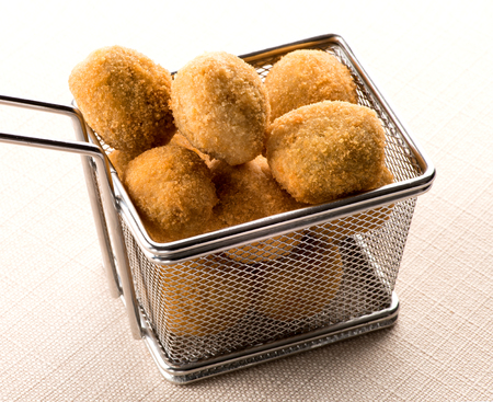 Wire frying basket filled with olive ascolane, or deep fried breaded stuffed olives with meat filling, a popular antipasti from the Marche region of Italy