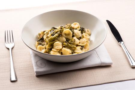Orecchiette con Cime di Rapa, oder eine Schüssel Orecchiette-Nudeln mit Brokkoli-Rabe, ein regionales Gericht aus Apulien, Italien, serviert in einer Schüssel am Tisch