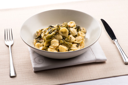 Orecchiette con Cime di Rapa, or a bowl of orecchiette pasta with broccoli rabe, a regional dish from Puglia, Italy served in a bowl at table