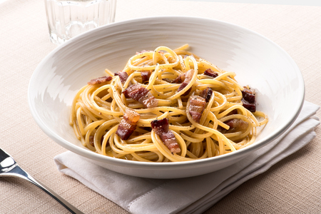 Spaghetti alla Carbanara from Lazio, Italy with egg, cheese, usually pecorino romano, pepper and guanciale or cured pork served in a bowl at table
