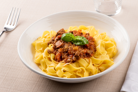 Tagliatelle al Ragù, a ribbon pasta with savory meat topping garnished with basil from Emilia Romagna region of Italy, served in a plain white bowl at table