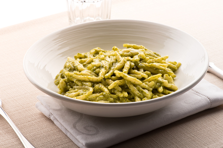 Trofie al Pesto, a regional twisted pasta with fresh basil pesto sauce from Liguria, Italy in a bowl on a napkin