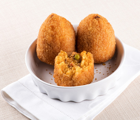 Arancini di Sicilia or fried stuffed rice balls from Sicily coated in breadcrumbs served in a bowl with one broken open to show the filling