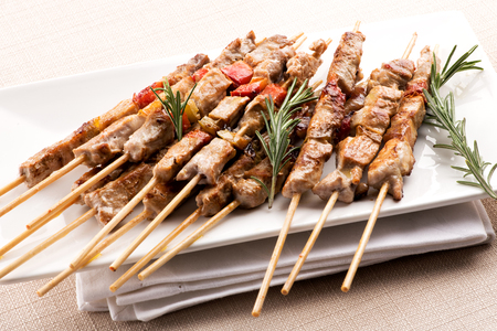 Savory marinated seasoned arrosticini from Abruzzo, Italy made from barbecued castrated lamb meat or mutton threaded on a skewer served with fresh sprigs of rosemary Banco de Imagens