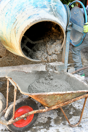 The technician worker loading cement into wheelbarrow pouring it out of electric concrete mixer for construction works