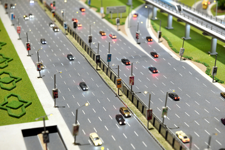 Model of city street with multi lane highway with traffic travelling in both directions and flyover to the right