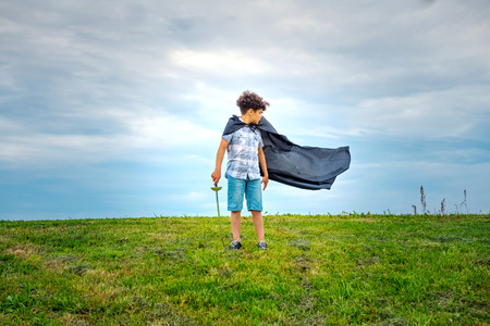 Young boy super hero with blowing cloak standing outdoors in a green field in the wind looking behind to watch it billow in the breeze