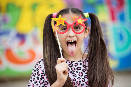 Fun young girl sticking out her tongue as she holds a party accessory of colorful glasses with stars to her eyes against a multicolored background