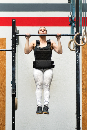 Atleta joven haciendo pull-ups ponderados en una barra con una chaqueta pesada para fortalecer los músculos de la parte superior del cuerpo en un concepto de salud y fitness Foto de archivo