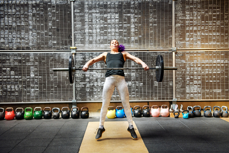 Young woman athlete doing the snatch with a barbell snatching it off the ground to lift it above her head in a single movement seen straining with effort as she raises the weight
