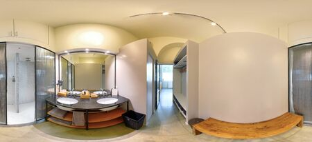 360 panorama of an empty gym bathroom interior with shower cubicles , hand basins or vanities with a mirror and wooden bench illuminated by down lights