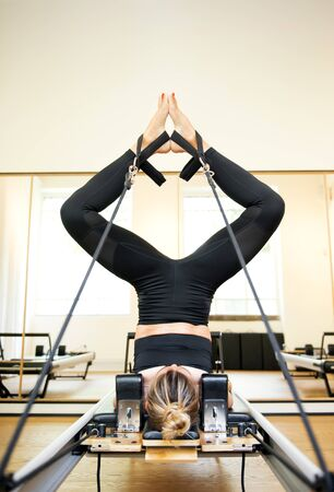 One young woman making short spine yoga pilates exercise in a workout room