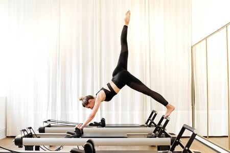 One woman doing single leg pike yoga exercise on reformer bed in a pilates gym