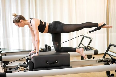 Fitted woman doing diagonal stabilization with strap exercise on a reformer pilates bed Banque d'images