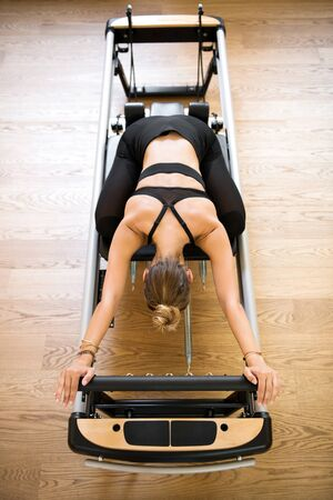 Overhead view on individual woman doing pilates stretch on reformer bed above hardwood floor Фото со стока