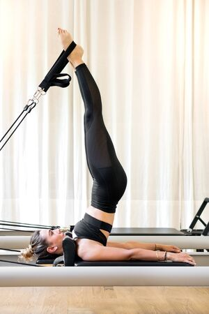 Individual woman in black doing short spine yoga exercise in a pilates gym Imagens