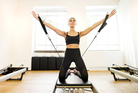 Single adult woman doing yoga arm work with straps exercise on reformer pilates bed