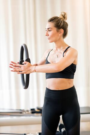 Fit young woman in black workout clothes using magic circle to exercise arms while in gymnasium