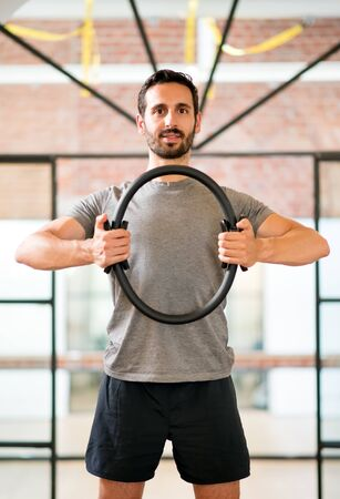 Fit man exercising arms with magic circle at gym