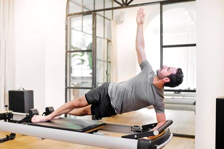 Fit man doing pilates side elbow plank exercises on a reformer bed in a gym in a health and fitness concept