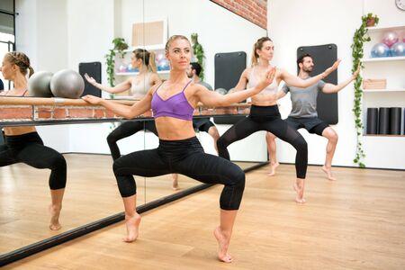 Grupo de personas que realizan ejercicios plie de segunda posición utilizando la barra de botín en un gimnasio reflejado en el espejo junto a un concepto de salud y fitness