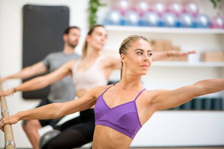Group of people doing spinal twist exercises using the barre in a gym with focus to a fit athletic toned woman in the foreground in a health and fitness concept