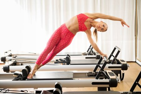 Woman doing standing mermaid stretch on pilates reformer bed at gym