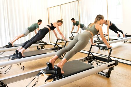 Group of friends doing pilates plank exercises pushing up on extended arms on reformer beds in a gym