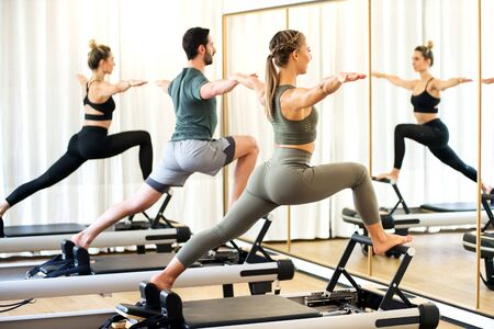 Class in a gym doing pilates standing lunges on reformer beds to stretch and tone the muscles reflected in a wall mirror Фото со стока
