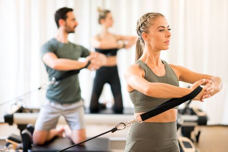 Woman with people in background training torso rotation using equipment at gym
