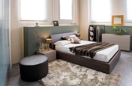 Intérieur de chambre monochrome marron de luxe moderne avec grande tête de lit au-dessus d'un lit double avec armoires, pouf et armoire intégrée Banque d'images