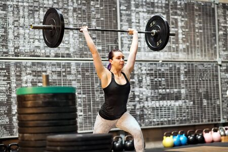 Young woman performing a clean and jerk exercise in a gym during training lifting the barbell above her head with extended arms after first moving it to a racked position