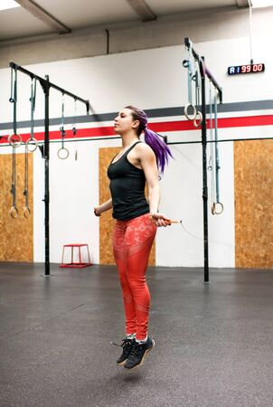 Fit muscular woman athlete exercising with a skipping rope inside a gym during her workout in a full length side view in a healthy active lifestyle or fitness concept
